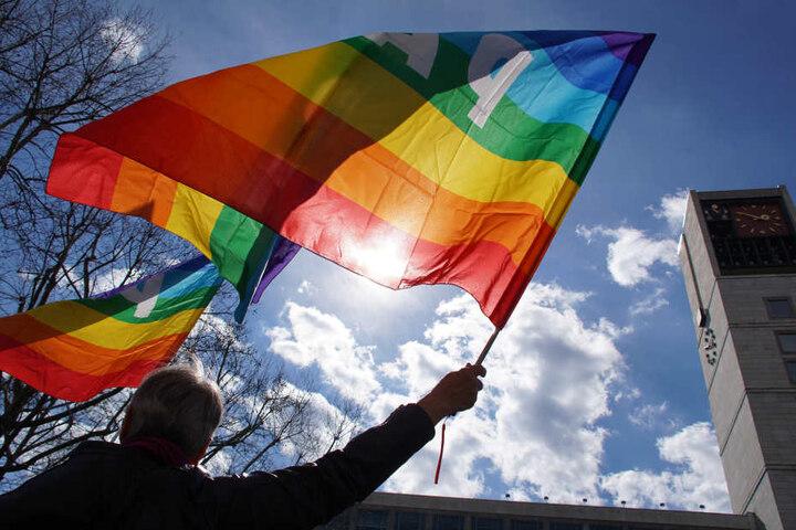 """Eine Frau hält eine Fahne hoch, auf der """"Pace"""" steht, lateinisch für Frieden."""