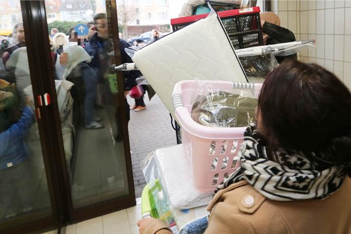 Über und über mit Waren beladen verlässt eine Kundin den Discounter.