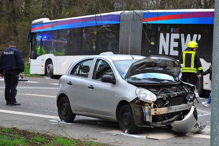 Ein Polizist steht an einer Unfallstelle hinter einem stark beschädigtem PKW und vor einem Bus.