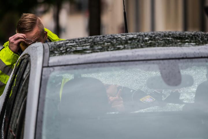 Zwei Polizeibeamte begutachten ein Fahrzeug mit beschädigter Heckscheibe im abgesperrten Bereich.
