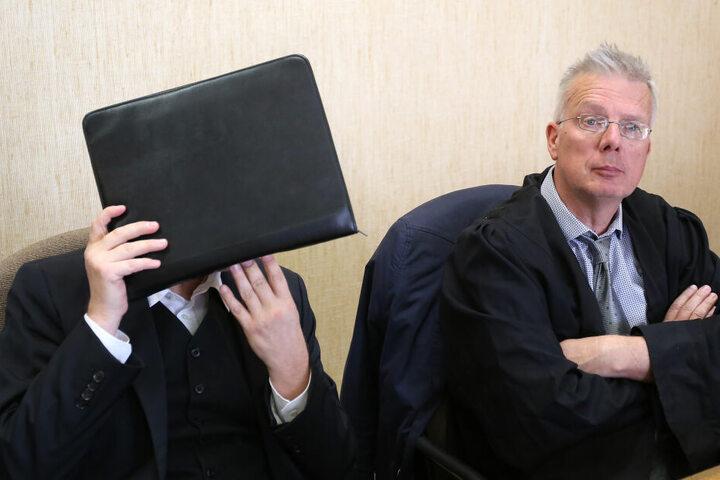 Der Angeklagte hält sich im Amtsgericht neben seinem Anwalt Konrad Schäfer (r) eine Aktentasche vor das Gesicht.