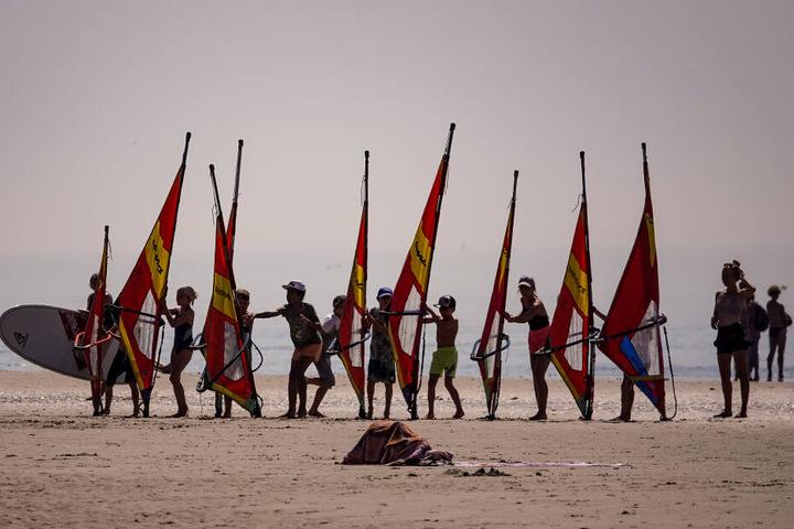 St. Peter-Ording: Teilnehmer einer Windsurfschule üben im Sommer mit den Segeln am Strand.