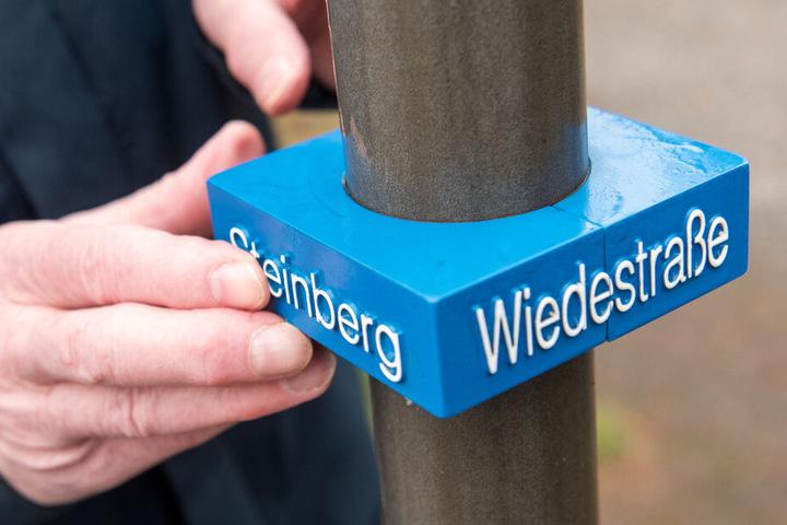 Am Mast des Straßenschilds wurde ein zusätzliches kleines Schild für Sehbehinderte montiert.