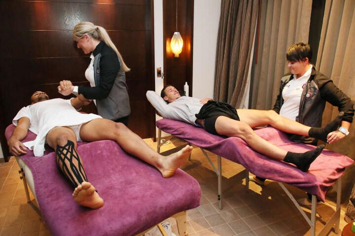 Die Physiotherapeutinnen Nadine Dörfel (l.) und Marie Koch bei der Arbeit. Sie kneten die Muskel von Malcolm Cacutalua und Dominik Wydra wieder weich. Meist geht ihre Schicht bis 23.30 Uhr.