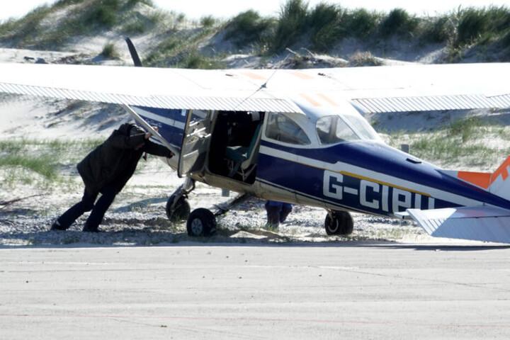 Die Besatzung schiebt das Flugzeug aus dem Sand zurück auf die Landebahn.