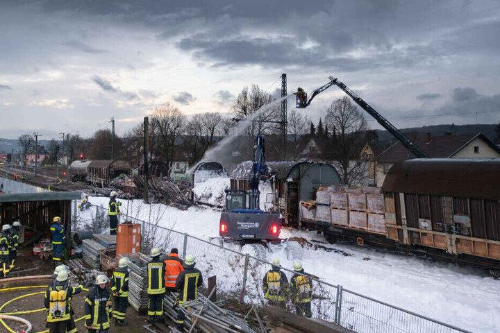 Ein Bagger des Technischer Hilfswerkes beseitigt Trümmer nach dem Brand der drei Güterwaggons.