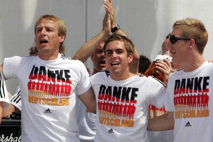 Die deutschen feiern die Vize-Weltmeisterschaft: Ex-Bundestrainer Jürgen Klinsmann (l.), Philipp Lahm (Mitte) und Bastian Schweinsteiger (r.).
