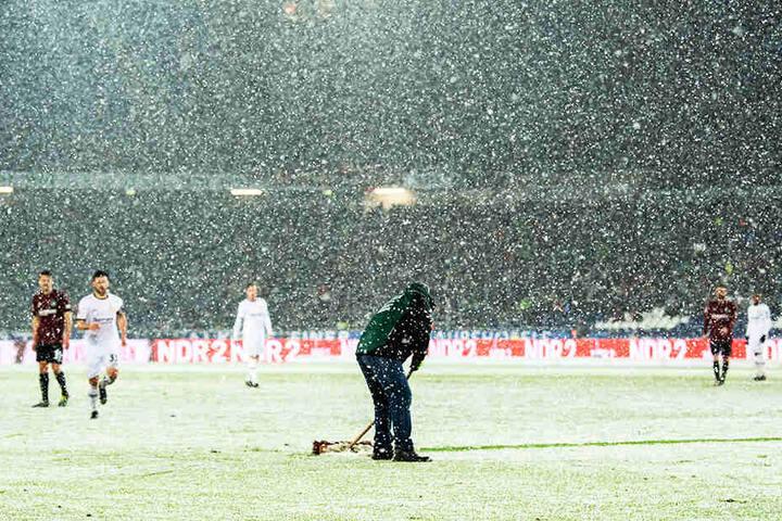 Die Helfer von Hannover 96 sind immer wieder im Einsatz, können dem starken Schneefall aber nur wenig entgegensetzen.