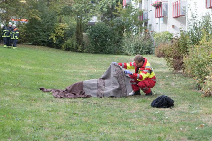 Unter einer Decke der Feuerwehr liegt das 50-jährige Opfer auf dem Rasen.