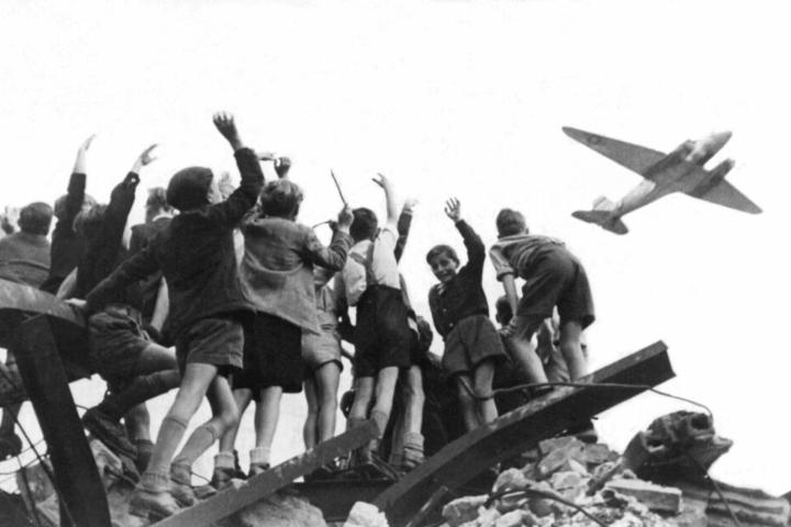 30.11.1947, Berlin: Das Foto aus dem Jahr 1948 zeigt West-Berliner Jungen, die auf einem Trümmerberg stehen, und einen US-amerikanisches Transportflugzeug, das Versorgungsgüter nach West-Berlin bringt, winken.