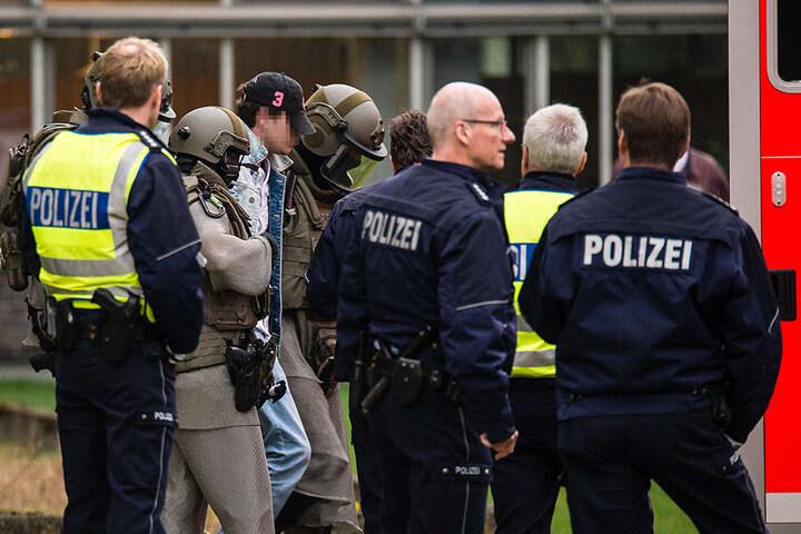 Der Mann versteckte sein Gesicht unter einer Baseball-Kappe, als er von der Polizei abgeführt wurde.