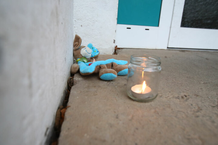 Vor dem Hauseingang haben Nachbarn zum Gedenken an die Toten Kerzen und Kuscheltiere abgelegt.