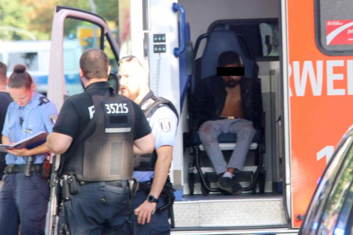Einer der festgenommenen Männer scheint eine Verletzung am Kopf zu haben. Seine Hände sind gefesselt und in Tüten gepackt.