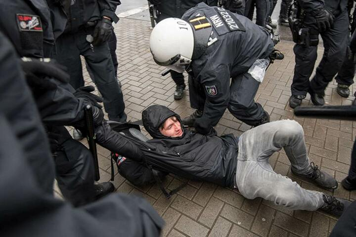 Ein Demonstrant wird von Polizisten davon getragen,
