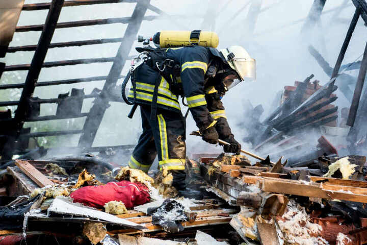 Ein Feuerwehrmann sucht im zerstörten Haus nach dem Vermissten.