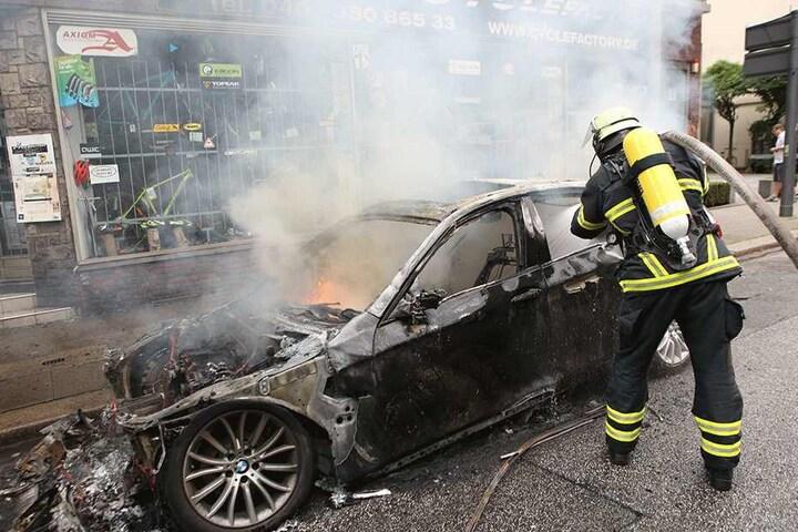 Hier kommt jede Hilfe zu spät: Ein Feuerwehrmann kann in Hamburg nur noch das ausgebrannte Wrack eines Autos löschen.