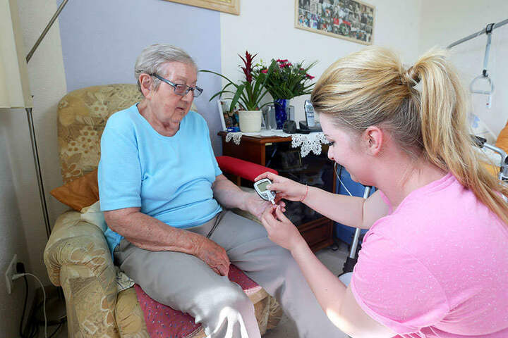 Schwester Stephanie (31) misst bei Ester Gerber (90) den Blutzucker und nimmt sich Zeit für einen kleinen Schwatz.