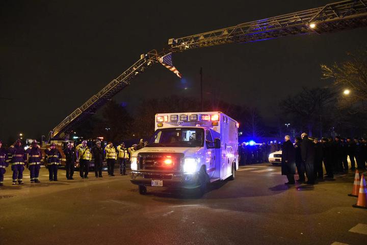Emotionaler Moment: Polizisten und Feuerwehrleute bilden eine Ehrengarde, als die Leiche des getöteten Polizisten zum Gerichtsmediziner gebracht wird.
