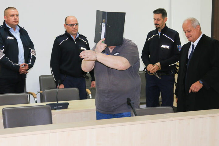 Der Angeklagte versteckte sich zu Beginn des Prozess hinter einem Aktenordner.