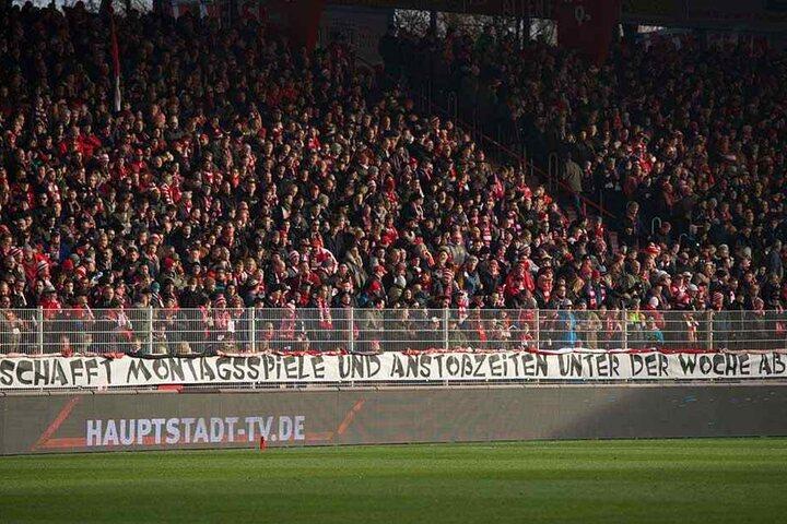 """Ein Banner hängt am Zaun der Gegentribüne in der Alten Försterei mit dem Schriftzug: """"Schafft Montagsspiele und Anstosszeiten unter der Woche ab!"""""""