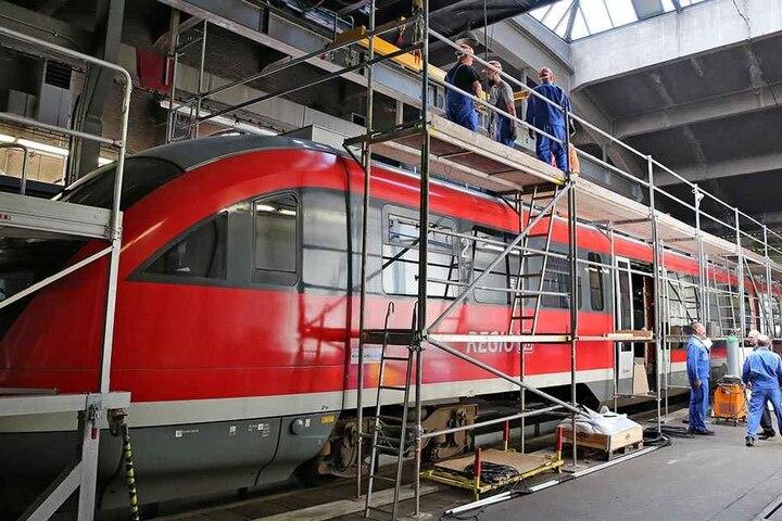Monteure verpassen einer Erzgebirgsbahn Zusatzaggregate auf das Dach eines Triebwagens.