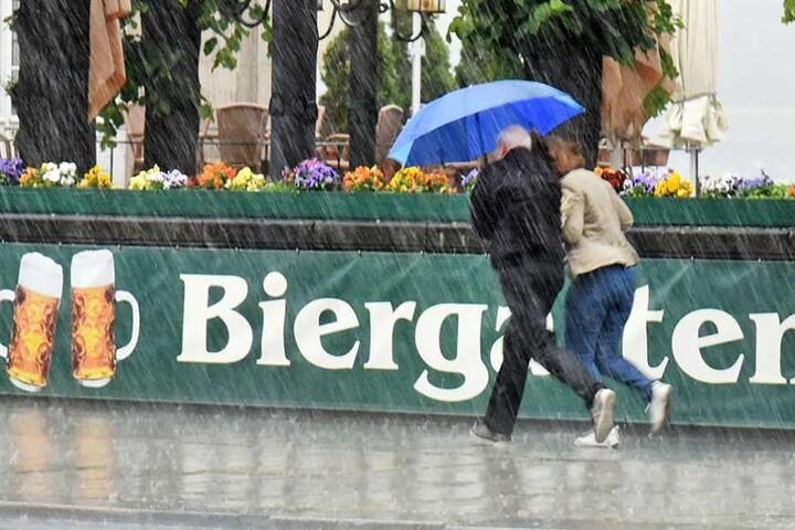 Ein Pärchen flüchtet unter dem Regenschirm aus einem Biergarten.