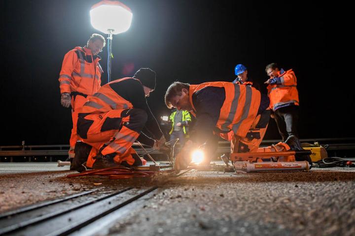 Techniker untersuchen auf der Autobahn A7 kurz vor dem Elbtunnel den Zustand einer Brückenlamelle.