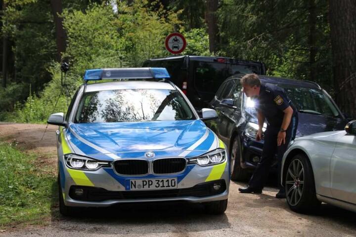 Ein Polizist steht auf einem Waldweg an einem Einsatzfahrzeug der Polizei. In einem Wald im Landkreis Nürnberger Land ist ein toter Mann gefunden worden. Die Kriminalpolizei hat die Ermittlungen aufgenommen.