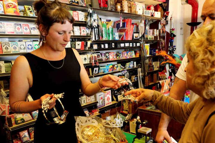 """Die Co-Inhaberin Kirsi Hinze (l) zeigt in ihrem Geschäft """"Zauberkönig"""" im Stadtteil Neukölln einer Kundin Utensilien für ein Kostümfest."""