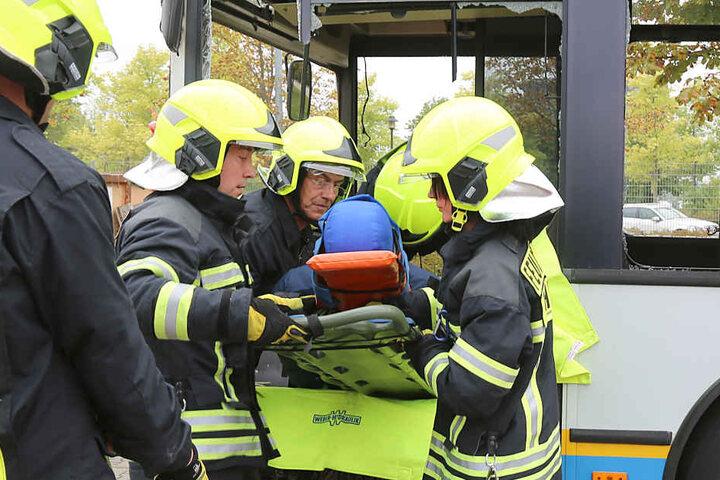 Vorsichtig heben die Feuerwehrleute den Verletzten aus dem Bus.
