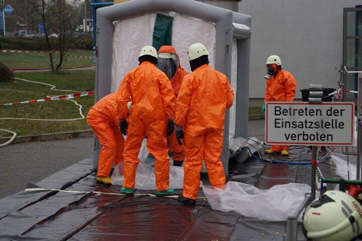 Einsatzkräfte tragen Schutzkleidung: Im Technikbereich soll Schwefelsäure ausgetreten sein.