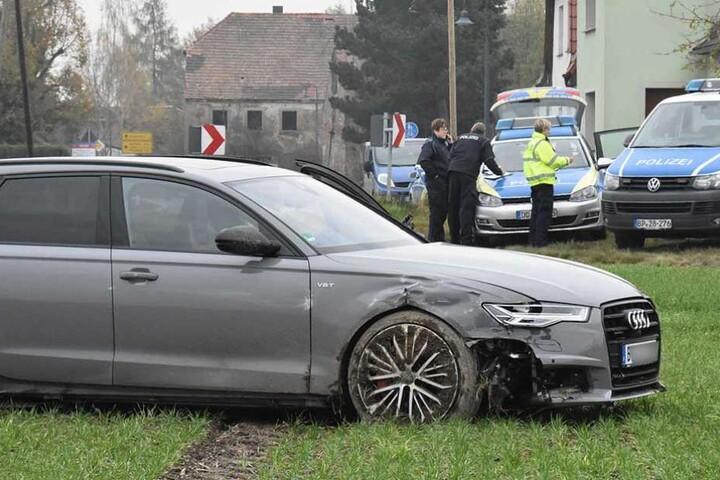 Der Audi steht auf der Wiese, im Hintergrund die Polizeifahrzeuge.