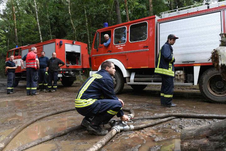 Feuerwehrmänner legen im Wald Schlauchverbindungen.