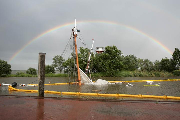 Dramatischer Untergang: Das gesunkene historische Segelschiff liegt fast gänzlich unter Wasser, während sich im Hintergrund ein Regenbogen aufspannt.