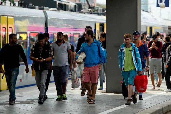 Flüchtlinge, die kurz zuvor mit einem Zug aus Salzburg angekommen sind, gehen auf dem Hauptbahnhof über einen Bahnsteig. (Archivbild)
