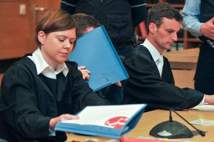 Der Angeklagte versteckt sich hinter einer Mappe.