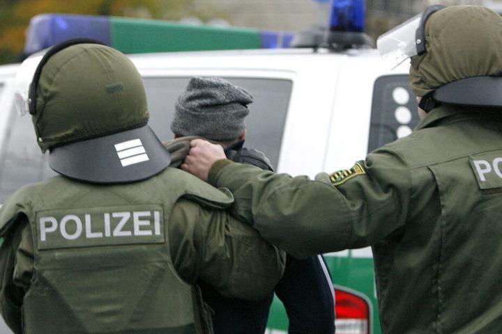 Ein Hooligan wird von zwei Polizisten abgeführt.