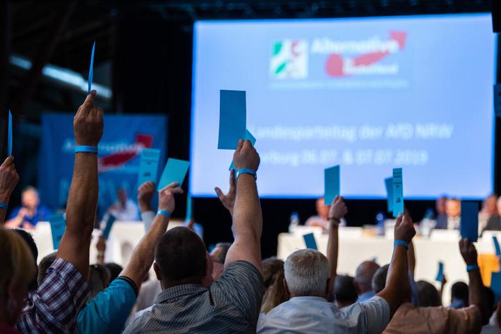 Delegierte halten beim Landesparteitag der NRW-AfD bei einer Abstimmung ihre Stimmzettel hoch.