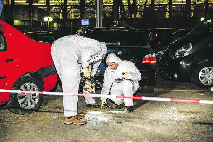 Zwei Beamte  sind mit der Spurensicherung auf dem Parkplatz beschäftigt.