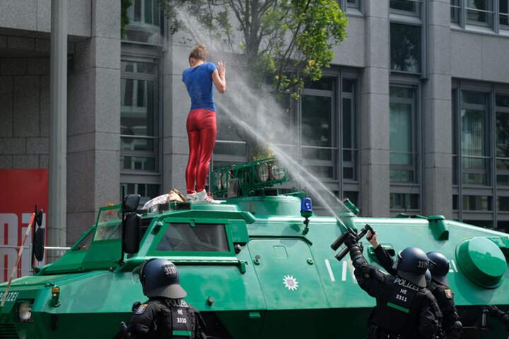 Eine junge Frau klettert auf ein Einsatzfahrzeug der Polizei und bekommt eine Ladung Pfefferspray ins Gesicht.