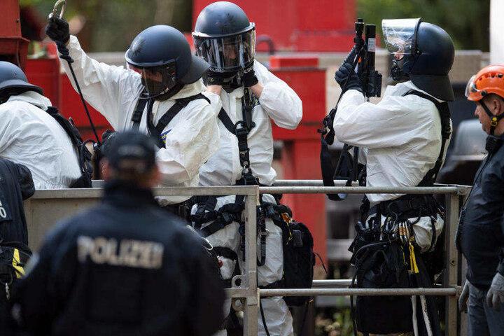 Polizisten tragen Schutzanzüge gegen den Bewurf mit Fäkalien.
