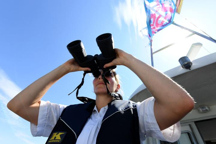 Eine Beamtin der Wasserschutzpolizei steht mit einem Fernglas am Heck eines Bootes. (Archivbild)