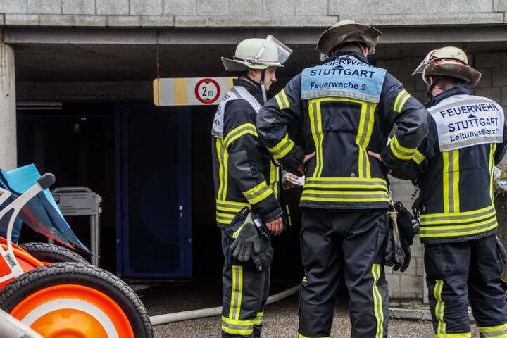 Feuerwehrleute vor einer Tiefgarage. Ein Mercedes hatte Feuer gefangen.