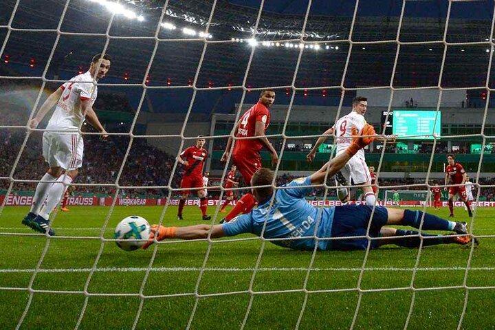 Leverkusens Torwart Bernd Leno (M) streckt sich vergeblich nach dem Ball von Münchens Robert Lewandowski (r), der das 0:2 erzielt.