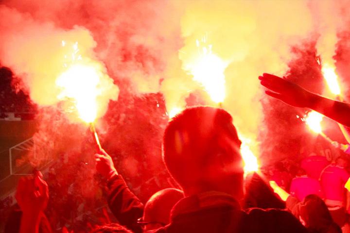 Einige Galatasaray-Anhänger zünden im Stadion bengalische Fackeln.