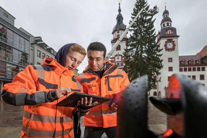Toni Wüstenhagen (20) und Ramtin Keshtkar-Rzaei (27) errechnen die Größe des Chemnitzer Weihnachtsbaums.