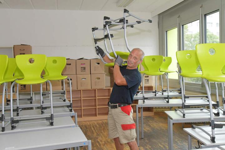 Während die Schüler ihre Sommerferien genießen, schleppt Umzugsmitarbeiter Ralf Erben (57) Bänke und Stühle.