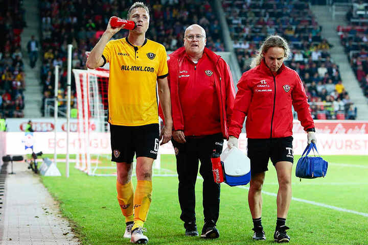 v.l.: Dynamos Kapitän Marco Hartmann wird nach seiner Auswechslung vom Mannschaftsarzt Dr. Tino Lorenz und Physio Tobias Lange begleitet.