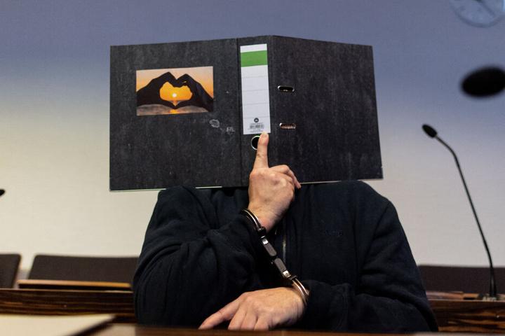 Der 58-Jährige hält sich vor Gericht einen Aktenordner vors Gesicht.