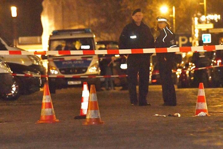 Polizisten stehen an der Stelle, wo zwei Männer angeschossen wurden.